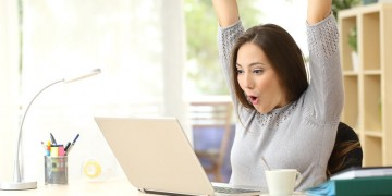 50532397 - euphoric and surprised winner winning online watching a laptop at home
